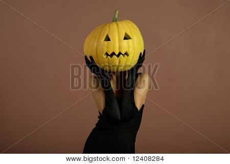 Sexy lady with big pumpkin on head. Surrealistic portrait.