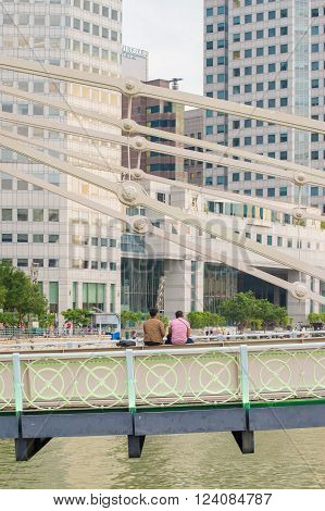 Singapore - Mar 26 2016: In late afternoon two male travellers sitting on Cavenagh Bridge looking at modern buildings in Raffles Place the financial center of Singapore.