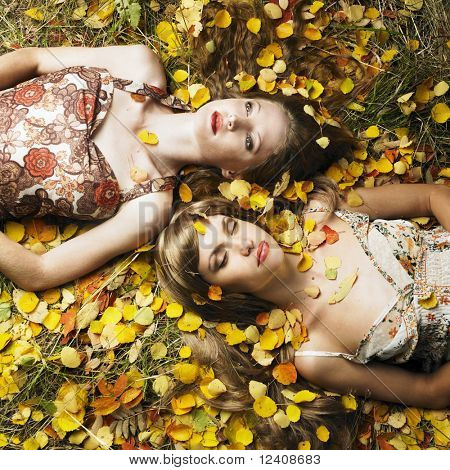 Two romantic girl lying in autumn leaves