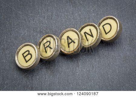 brand word in old round typewriter keys against gray slate stone