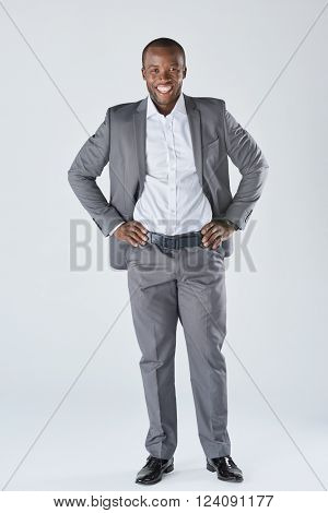 Full length portrait of approachable smiling black  professional in business suit isolated in studio