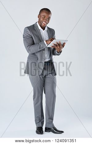 Full length portrait of positive friendly black  professional businessman with touchscreen tablet device in business suit isolated in studio