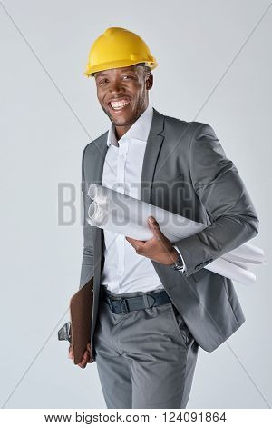 Smiling portrait of african black construction engineering consultant holding drawing plans and wearing a construction hardhat