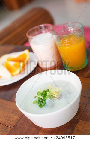Congee with minced pork in white bowl and orange juice, milk background on wood table. Thai food.