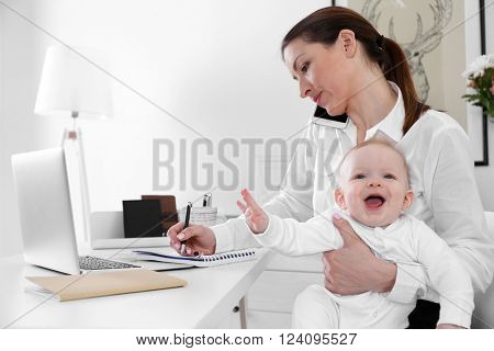 Businesswoman with baby boy working from home using laptop and mobile phone