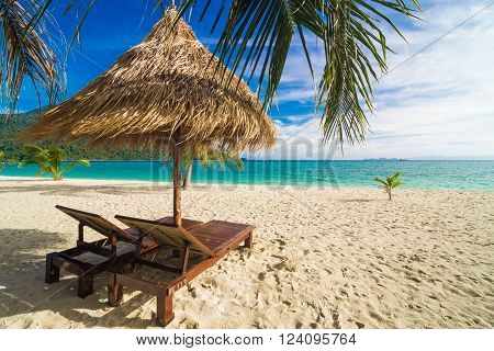 Vacation Time Background Of Two Beach Lounge Chairs Under Grass Tent