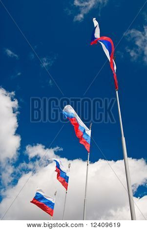 Four waving Russian flags with St.Petersburg symbol at the top over cloudy sky