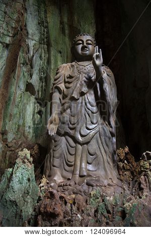 Sculpture of standing Buddha in the cave Tang Chon full face. Marble mountain, Danang, Vietnam