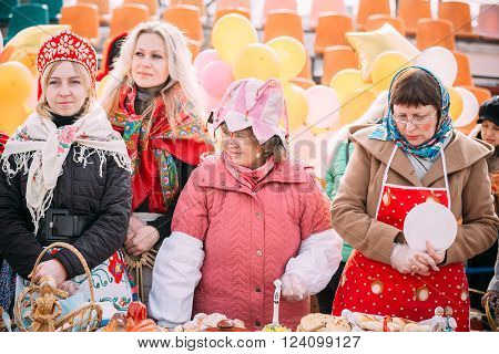 Gomel, Belarus - March 12, 2016: Four unknown beautiful women trading pastry at Celebration of Maslenitsa Shrovetide holiday