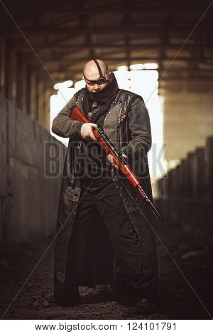 Portrait of big brutal man with rifle in leather coat as style of Mad Max at abandoned building.