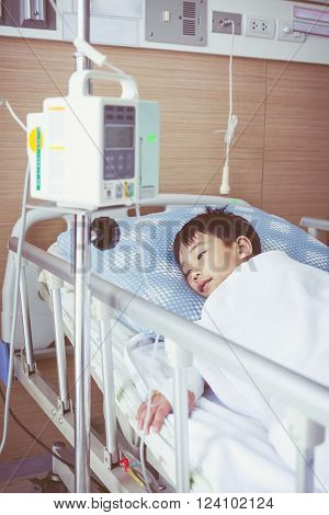 Asian Boy Lying On Sickbed With Infusion Pump Intravenous Iv Drip. Retro Style.
