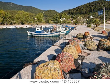 Multicolored fishing nets on the pier and fish boats in small harbour Skopelos island; Sporades; Greece