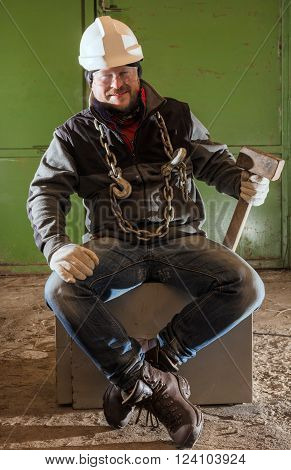 Tough worker in safety helmet with iron chain and sledgehammer