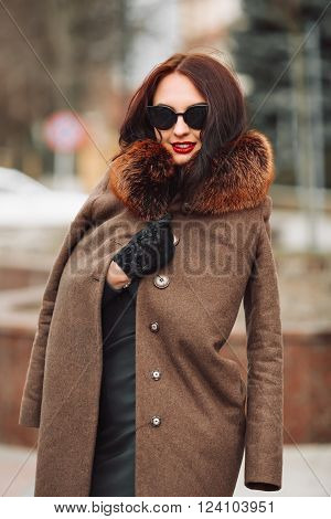 Brunette girl in an elegant green dress and fur coat with a fluffy fur, gloves and stylish sunglasses outdoors. young woman with chic long dark hair and trendy makeup,