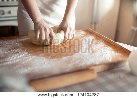 Baker hands kneading dough in flour on table
