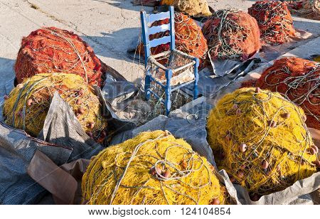 Red and yellow fishing nets and blue chair in the center on the pier Skopelos island; Sporades; Greece