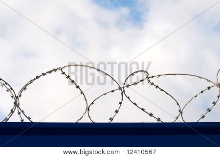 Fence with barbed wire over cloudy sky