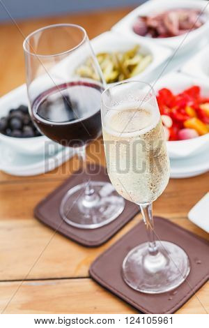 Two Glasses of Sparkling Wine and Red Wine on a wooden table.