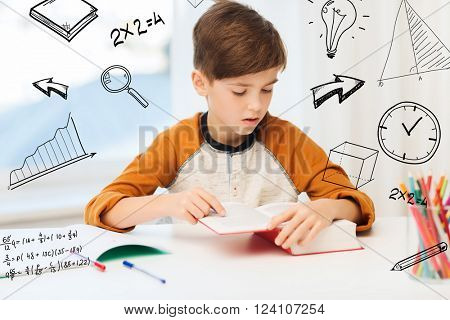 education, childhood, people, homework and school concept - student boy reading book or textbook at home over mathematical doodles
