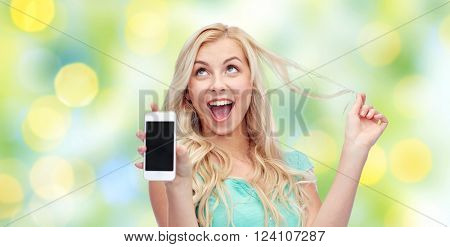 emotions, expressions, technology, summer and people concept - smiling young woman or teenage girl showing blank smartphone screen over green lights background