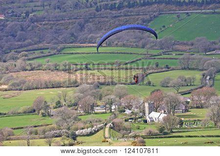 Paraglider flying above Sourton church on Dartmoor