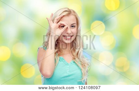 fun, emotions, expressions, summer and people concept - smiling young woman or teenage girl making ok hand gesture over green lights background
