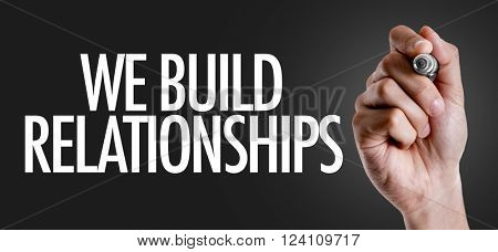 Hand writing the text: We Build Relationships