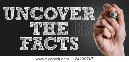 Hand writing the text: Uncover the Facts