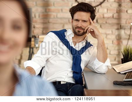 Portrait of smiling young businessman, sitting desk, elbowing, looking at camera.