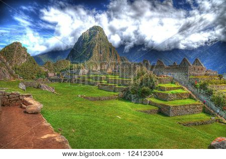 Colorful HDR image of tourists visiting the ruins in Machu Picchu the lost Incan City of Machu Picchu near Cusco on a clear blue sky