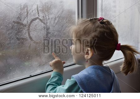 little girl draws a finger the sun on the misted wet glass