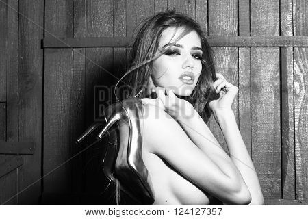 Sexy sensual mysterious naked young woman with long beautiful windy hair style holding golden shoes near bare chest on wooden background horizontal picture