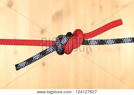 two ropes with two knots on wooden background