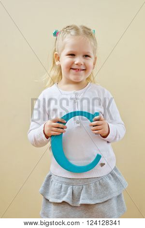 toddler girl is standing with letter B