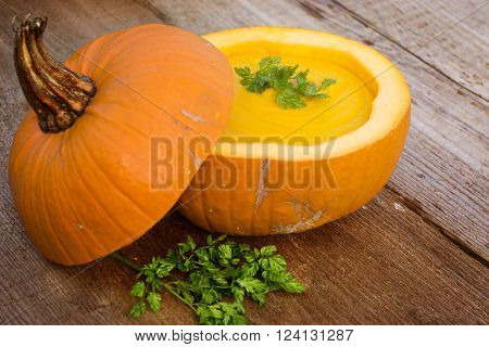 pumpkin soup in hollowed-out pumpkin on an old table