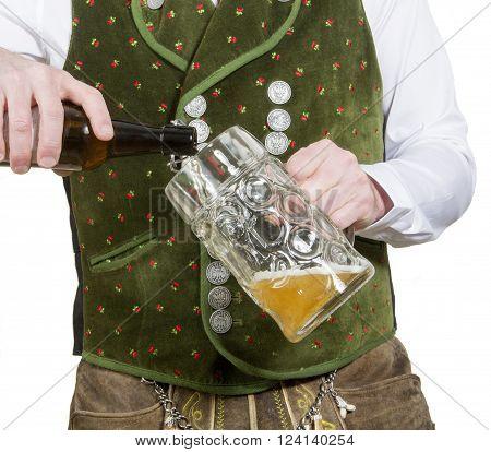 closeup of bavarian man pouring beer in a big mug