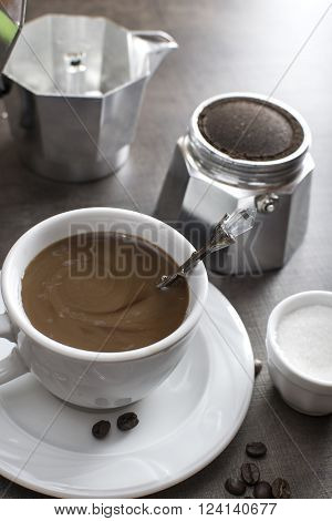 Cup of coffee with coffee maker on wooden backround