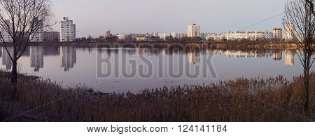 GOMEL BELARUS - MARCH 27 2016: Beautiful view of evening Gomel with reflection in the lake. Volotova