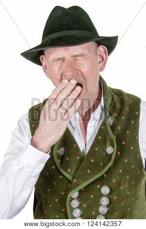 portrait of tired yawning man wearing traditional bavarian clothes