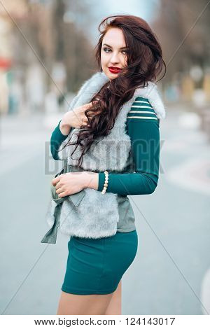 Winter time fashion for women. Woman wearing sweater fur vest belt and pendant in freezing cold time