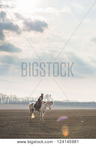 Woman and horse outdoor. Dramatical sky and empty field. White horse and horse rider woman posing outdoor.