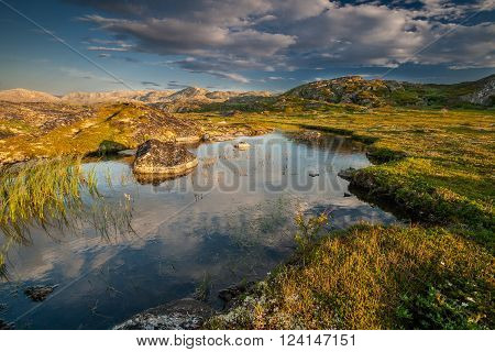 Small lake behind a polar circle lit with the northern summer sun