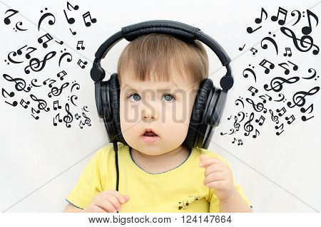 Music sheets from the headphones when little girl listening music