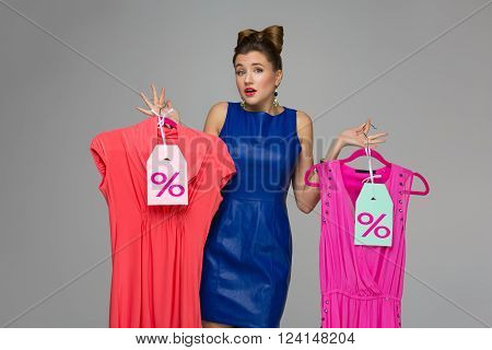 Beautiful confused woman holding  two dresses on hangers. Price tags. Over grey background. Copy space.