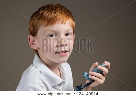 Little boy with asthma holding his inhaler.