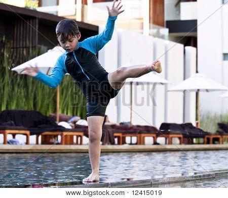 Balancing 5Yr Old Boy At Swimming Pool, One Leg