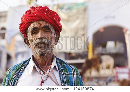 Pushkar, India - January 23, 2013: Unidentified Rajasthani man wearing traditional red turban in the sacred town of Pushkar in Rajasthan, India.
