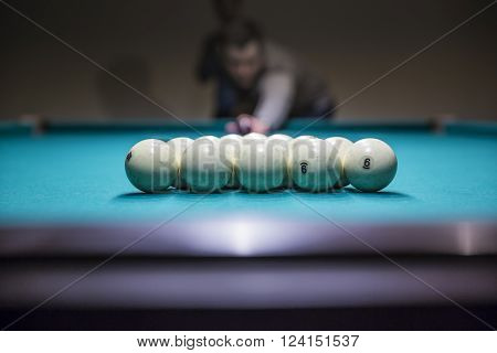 Man in  prepare for start game of billiard balls with triangle. 2016