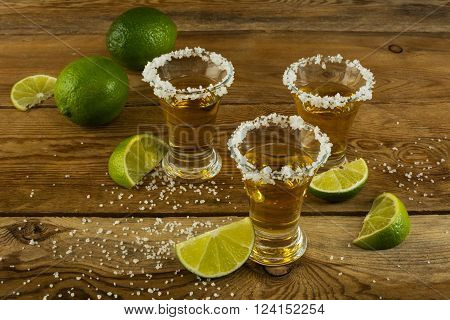 Three tequila shots with lime and salt on the wooden background. Gold Mexican tequila. Tequila shot. Tequila