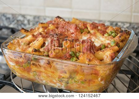 meaty baked rigatoni with peas bolognese ragout mozzarella and cheese in an oven pan of glass ** Note: Shallow depth of field